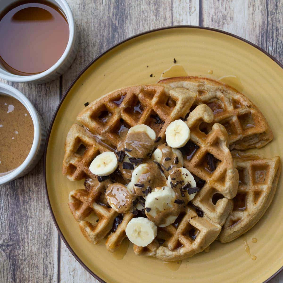 Overhead view of protein waffles topped with sliced bananas, shaved chocolate almond butter and syrup.