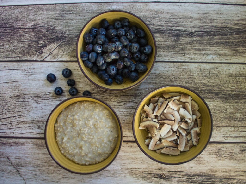 Overhead shot of three bowls showcasing oatmeal and toppings.