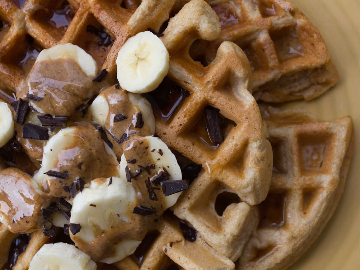 Up close image of waffle with banana, chocolate and syrup on it.