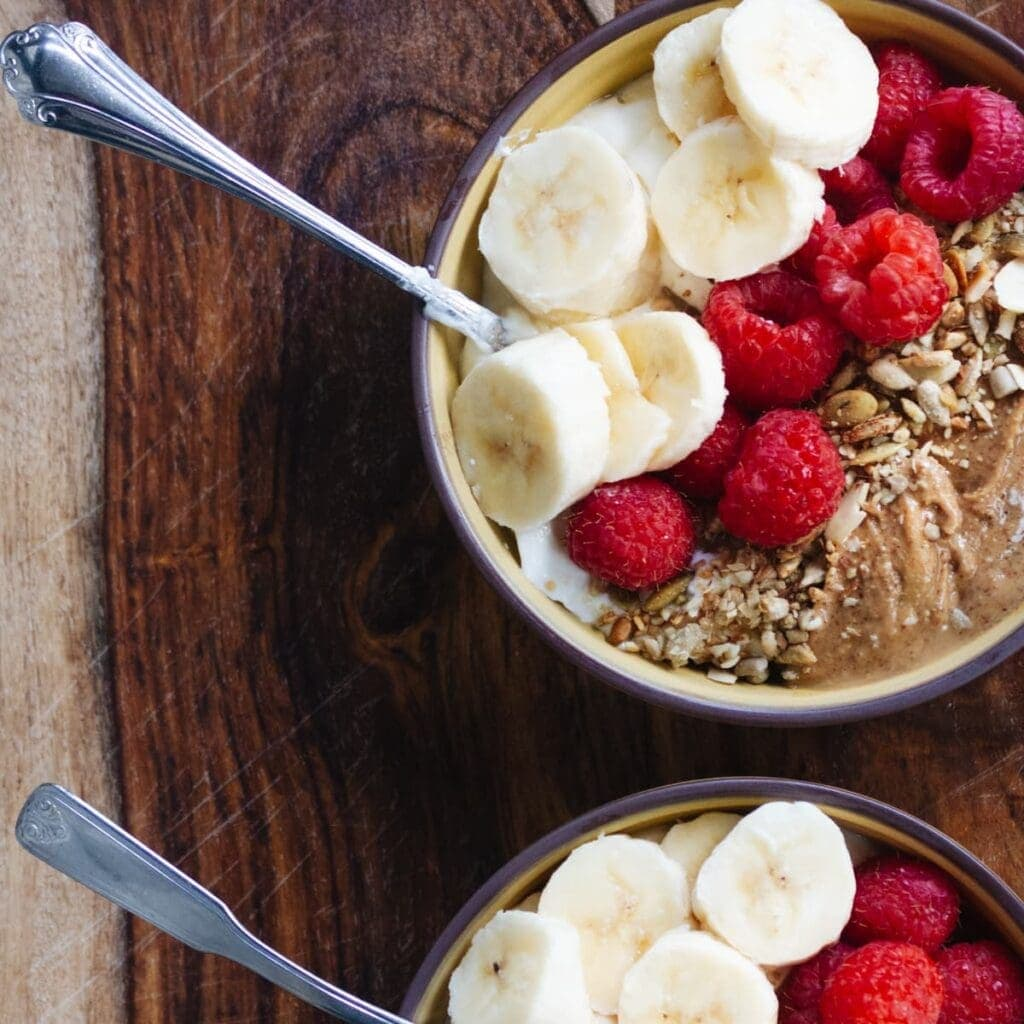 Overhead shot of almond butter breakfast bowl on wooden table. Topped with banana and raspberries.