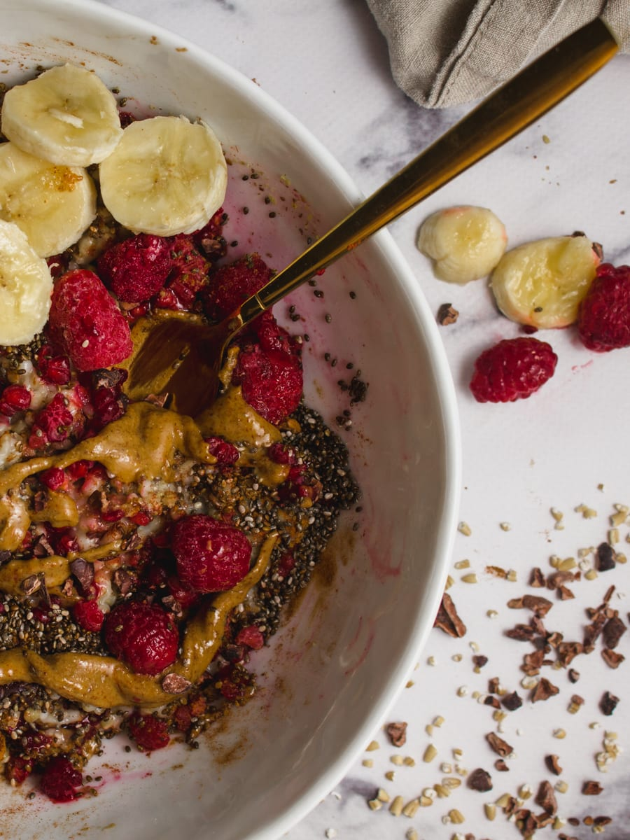 A bowl of healthy oatmeal that's topped with creamy almond butter, raspberries and other superfood ingredients.