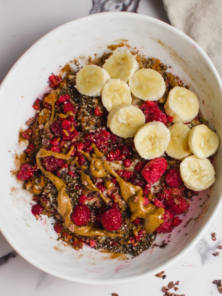 Healthy porridge with rasberries, almond butter, and other high protein toppings.