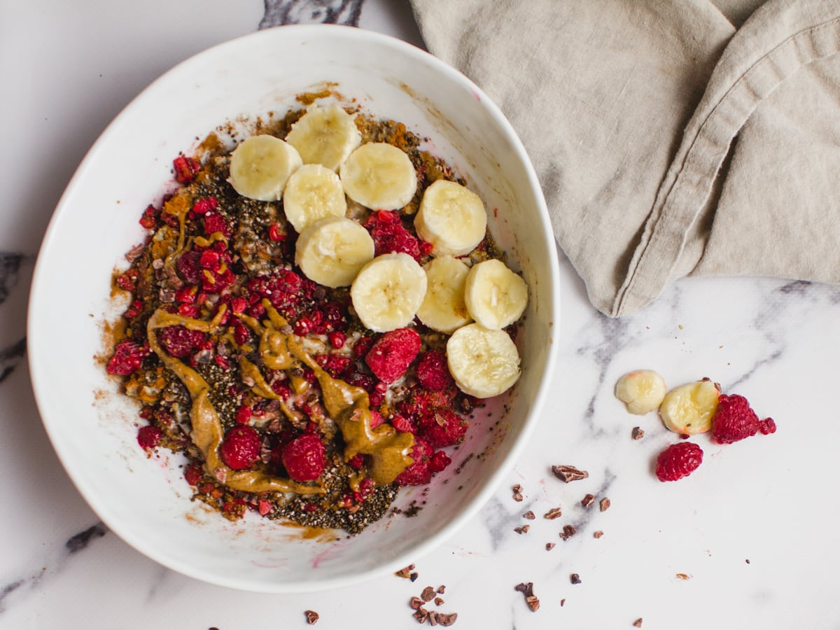 Healthy oatmeal bowl with raspberries, almond butter, banana, chia seeds, ground flax seed and cacao nibs.
