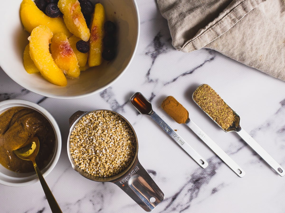 Ingredients in healthy oatmeal breakfast recipe with peaches shot from overhead
