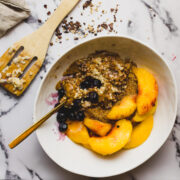 Bowl of oatmeal with peaches and blueberries