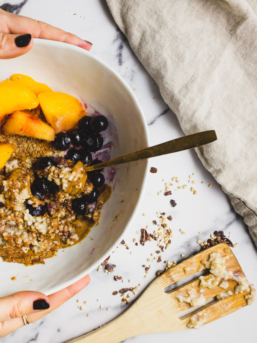 Oatmeal with peaches, blueberry, ground flaxseed and almond butter.