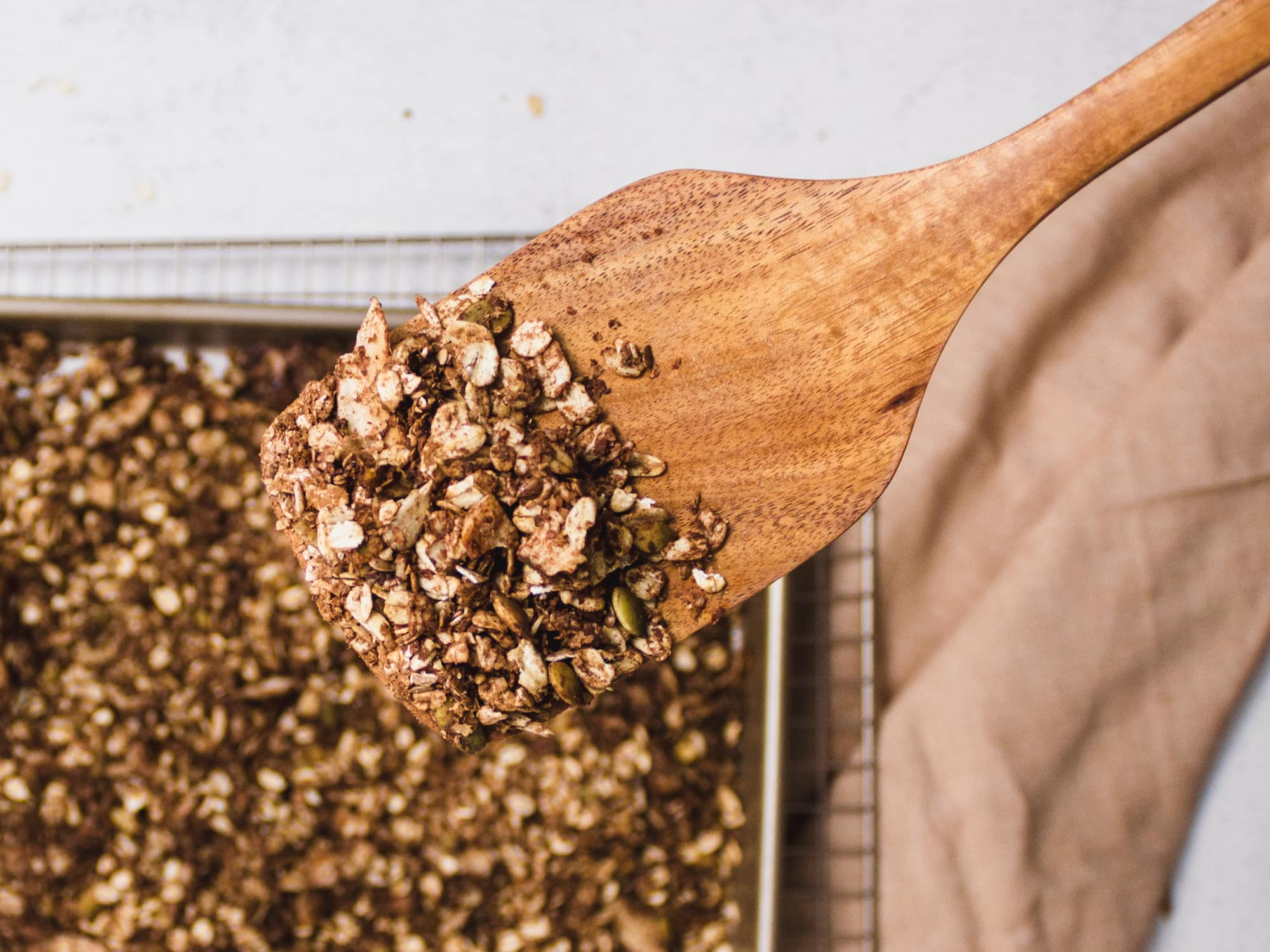 A wooden spoon filled with finished chocolate granola fresh out of the oven. Has a pink napkin in the background.