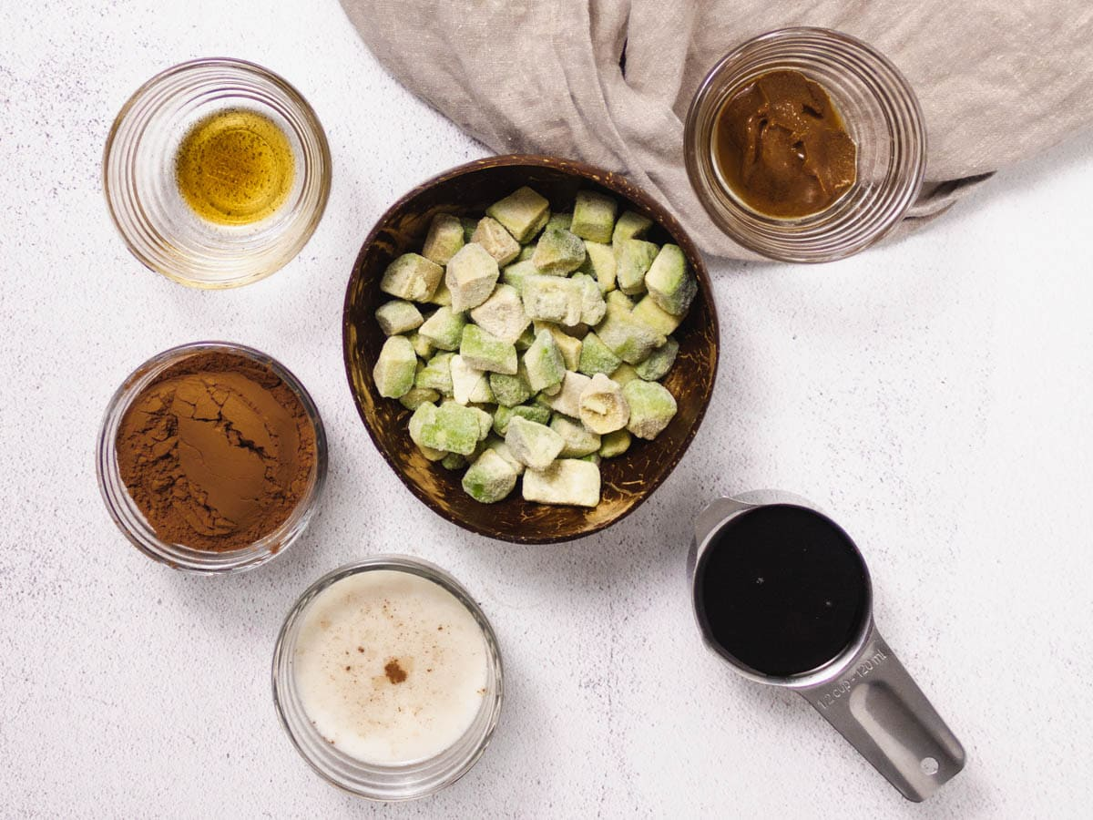 Overhead shot of all ingredients needed to make avocado pudding. Maple syrup, almond milk, cocoa powder, avocado, vanilla extract and almond butter.