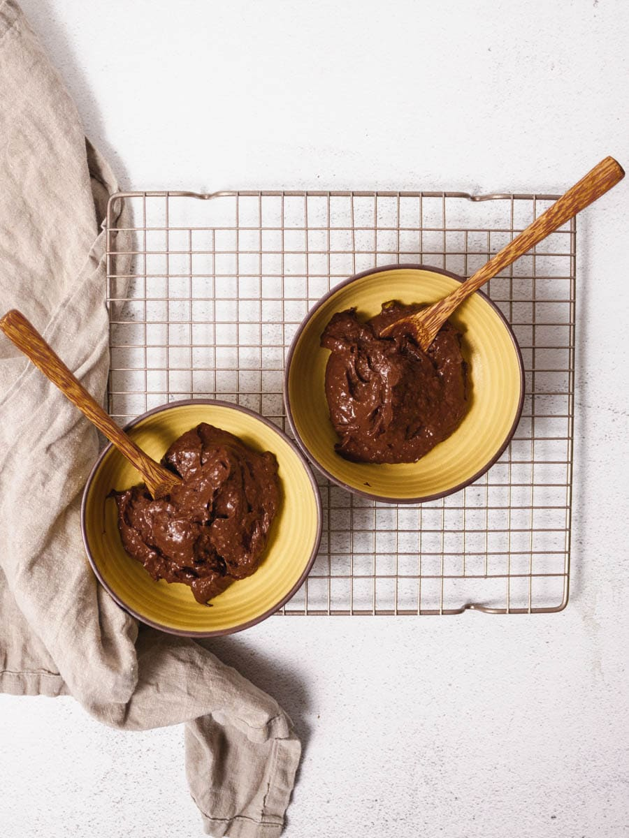 Overhead shot of two bowls of avocado chocolate mousse. They are on top of cooling rack. Both have a wooden spoon in them.