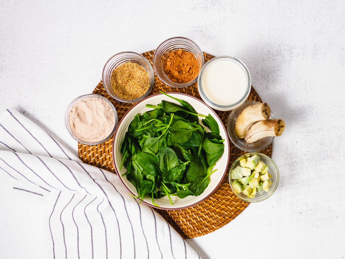 Overhead shot of ingredients needed to make a chocolate banana protein smoothie. Includes protein powder, flaxseed, cocoa powder, nut milk, banana, avocado and spinach.
