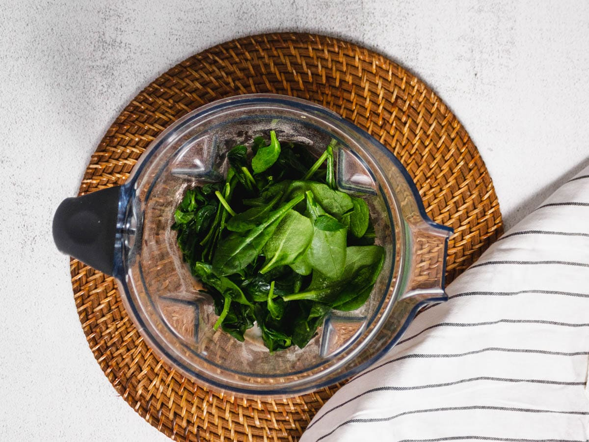Overhead shot of a blender on a wooden placemat and white countertop. It is filled with frozen greens.