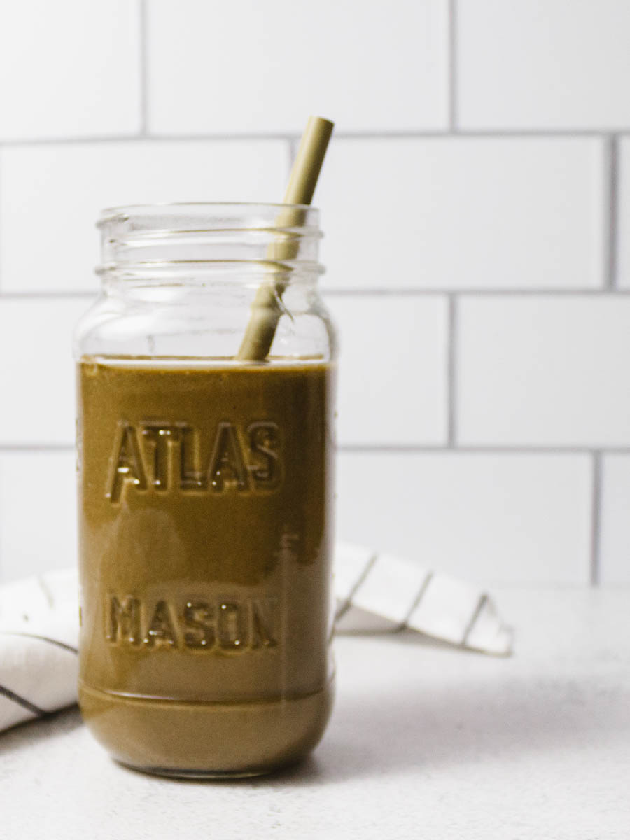 A mason jar filled with a healthy chocolate banana smoothie on a white countertop.