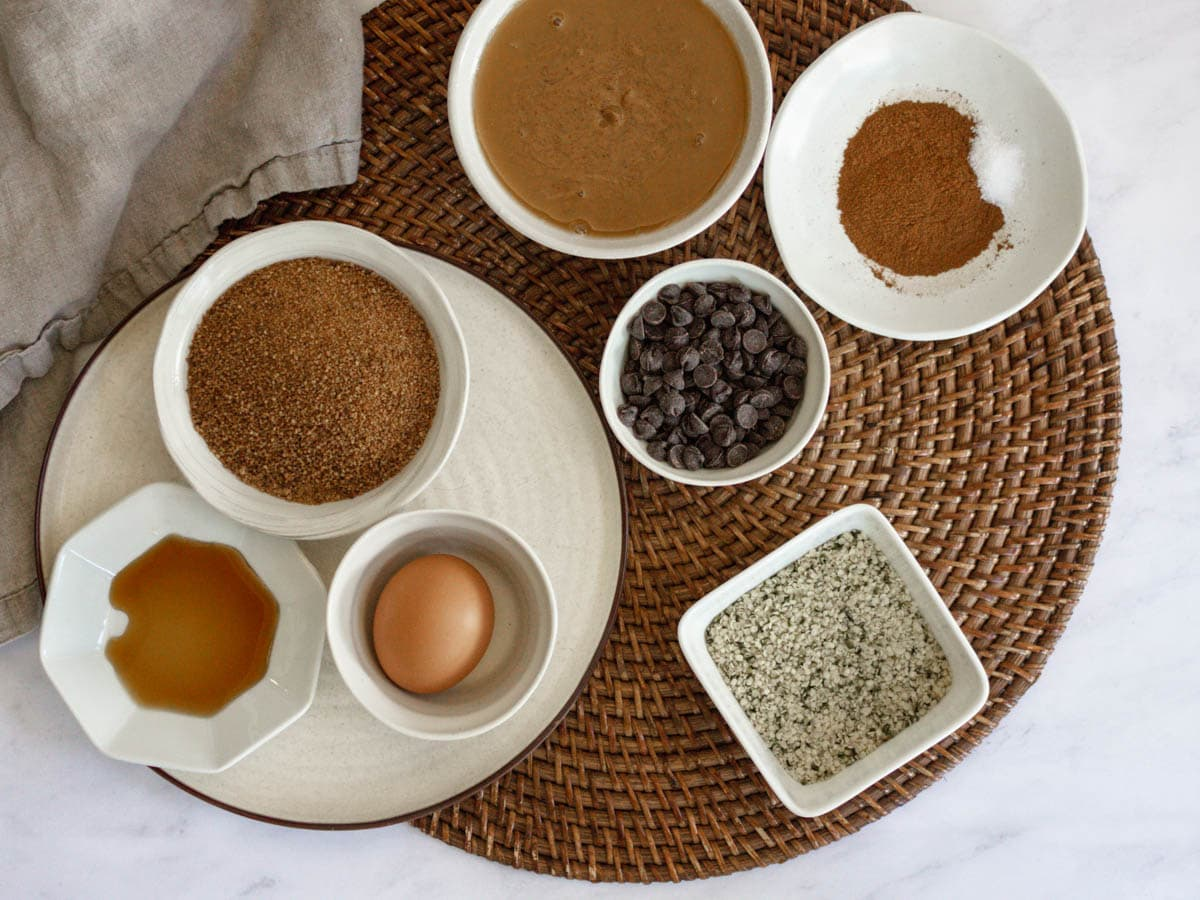 Overhead shot of ingredients needed to make hemp cookies. They are on top of a rattan placemat on a white countertop.