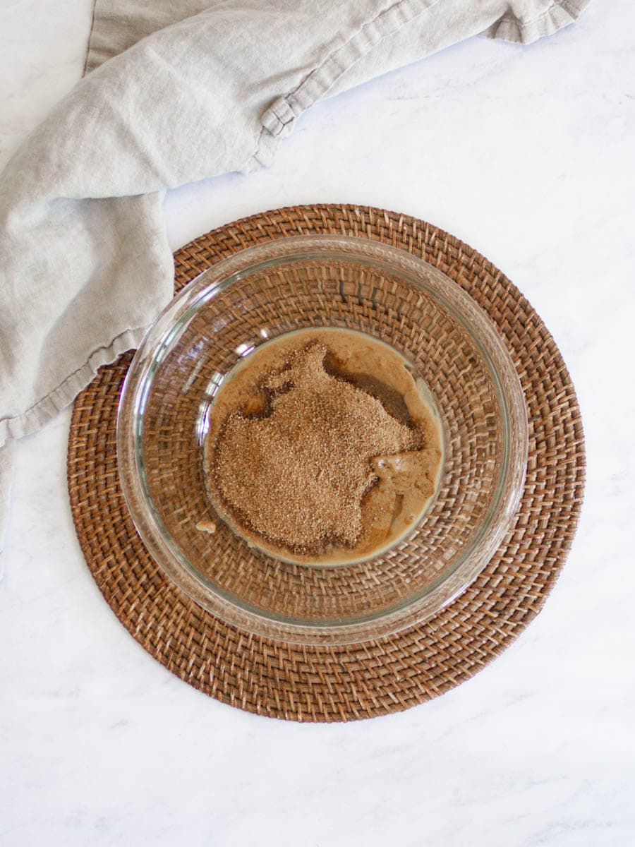 Glass bowl on rattan placemat. It is filled with ingredients needed to make hemp heart cookies. There is a linen dish cloth beside.