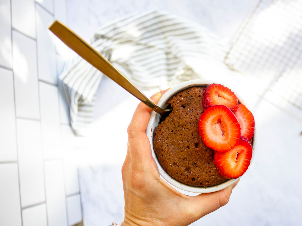 A hand holding a white ramekin that has a paleo chocolate brownie topped with sliced strawberries.