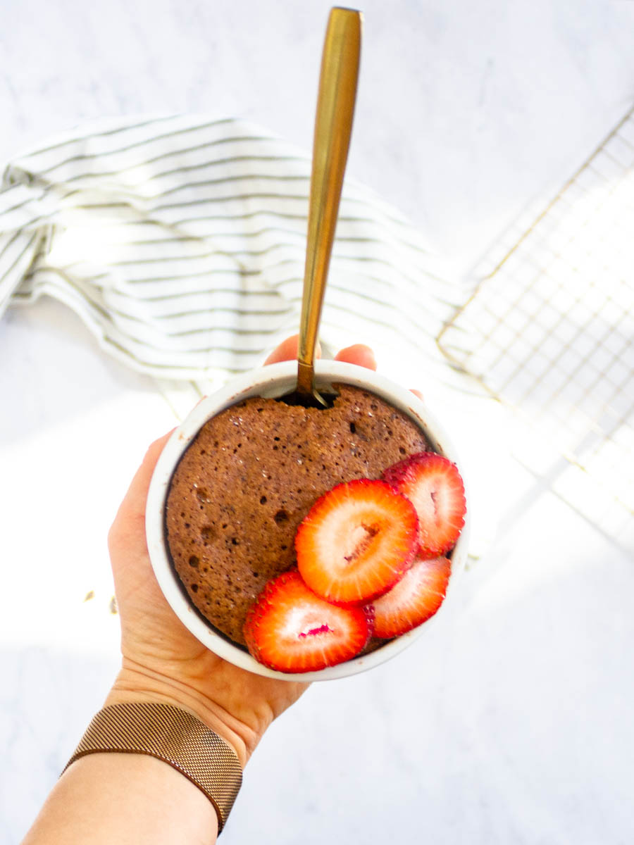Finished paleo mug cake in white ramekin, being held by hand. It's topped with sliced strawberries.