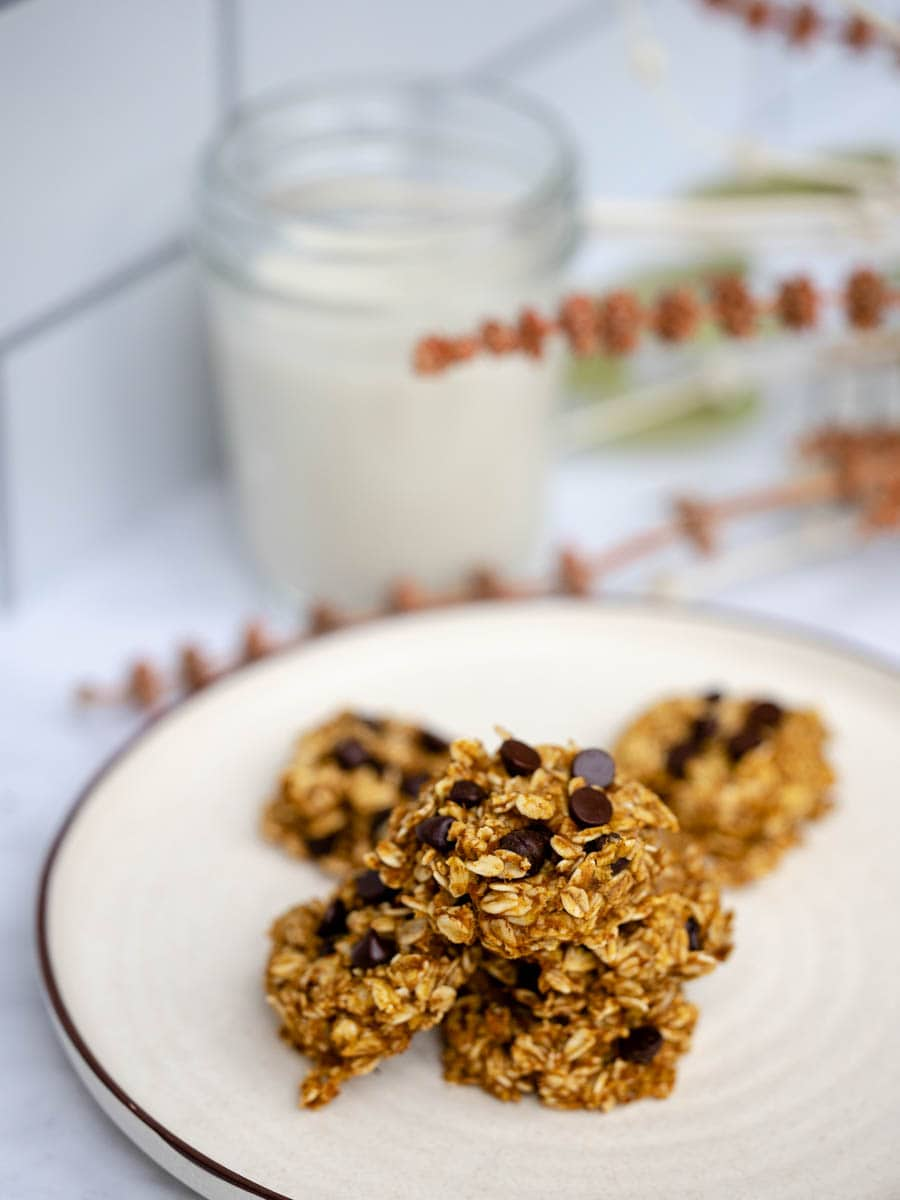 A pile of healthier pumpkin chocolate chips cookies on a stoneware plate. A glass of milk is in the background.