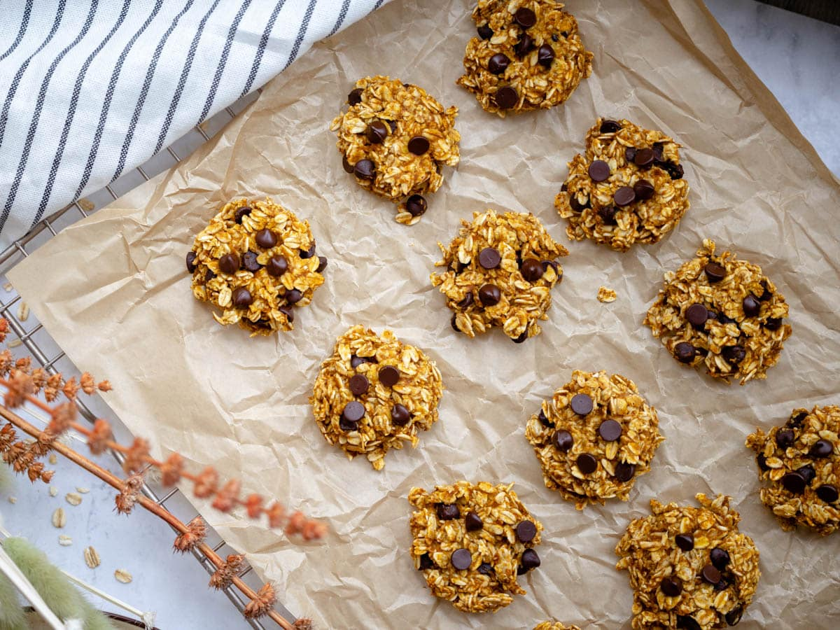 Healthier pumpkin cookie dough balls on a baking tray with parchment paper. They have been flattened with a fork. Autumn dried flowers outline the scene.