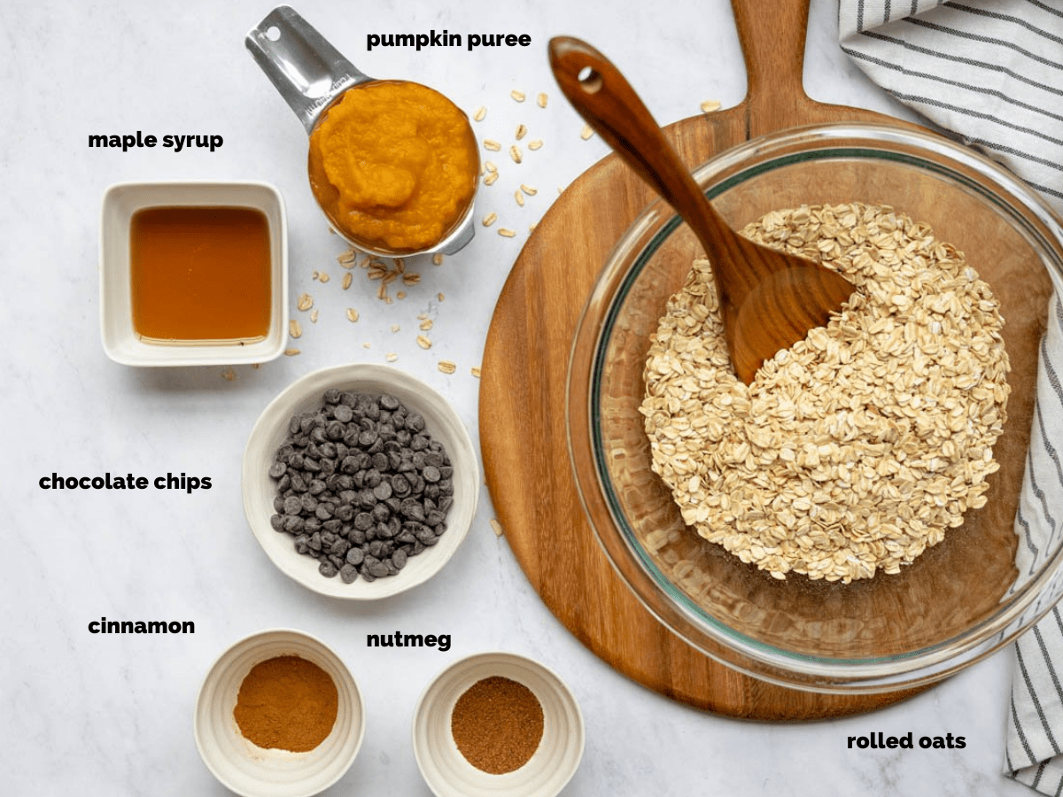 Overhead shot of ingredients needed to make healthier pumpkin oatmeal cookies. A striped dish towel outlines the scene.